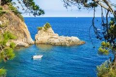 在肋前缘Brava,卡塔龙尼亚,西班牙的峭壁旁边乘快艇 免版税库存照片