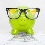在股市图的绿色存钱罐与100美元钞票-一对一比率 库存图片