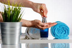 在肥皂分配器的人手在卫生间里 图库摄影
