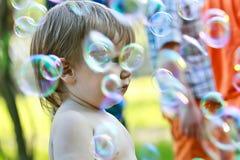 在肥皂泡中的男孩 免版税库存图片