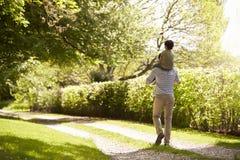 给在肩膀的父亲背面图儿子乘驾在步行期间 免版税图库摄影