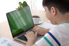 在肩膀键入在计算机lapt的射击了Asain男孩 库存照片