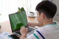 在肩膀键入在计算机lapt的射击了Asain男孩 库存图片