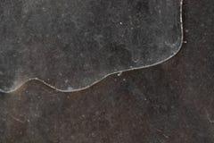 在肮脏和多灰尘的玻璃的长的弯曲的裂缝在一个被放弃的大厦 图库摄影