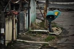 在肮脏和被放弃的路面的公用电话箱子 库存图片
