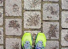 在肮脏的具体砖顶视图的绿色跑鞋 免版税库存照片
