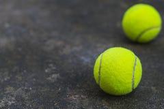 在肮脏的地面上的网球 免版税库存图片