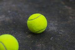 在肮脏的地面上的网球 免版税库存照片