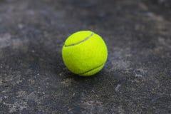 在肮脏的地面上的网球 免版税图库摄影