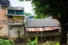 在肮脏的河附近的贫民窟有由锌照片做的屋顶的拍在德波印度尼西亚 免版税库存照片