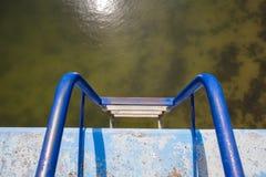 在肮脏的游泳池的蓝色梯子 免版税库存图片