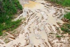在肮脏的路泥的汽车车轮痕迹 库存图片