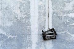 在肮脏的水泥墙壁上的老打破的电源插座 免版税库存图片