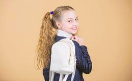 在背包的运载的事 女小学生与小背包的马尾辫发型 怎么学会适合的背包恰当地 ?? 免版税图库摄影