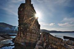 在背后照明的峭壁与在Kassiopi的光束在科孚岛, Gre沿岸航行 库存照片