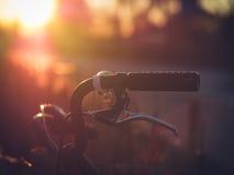 在背后照明的年迈的老自行车把手 库存图片