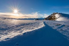 在背后照明,在阿尔卑斯的明亮的晴天冬天的雪山,发光在高积雪覆盖的山峰的太阳 图库摄影
