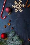 在背景、树枝、圣诞节玩具、雪花、糖果和核桃仁 免版税库存照片