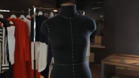 在背景光的空的黑时装模特是在演播室中间 以垂悬的礼服的形式逗人喜爱的玩具  图库摄影