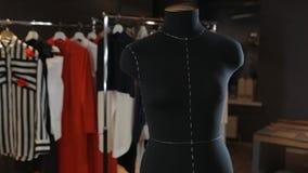 在背景光的空的黑时装模特是在演播室中间 以垂悬的礼服的形式逗人喜爱的玩具  免版税图库摄影