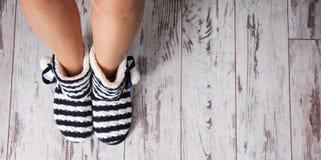 在背景地板上的温暖的拖鞋 免版税库存图片