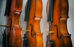 在背景堆积的三把小提琴抽象派设计背景  显示木头的边在小提琴、葡萄酒和艺术样式的 免版税图库摄影