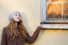在背景墙壁上的女孩 免版税图库摄影