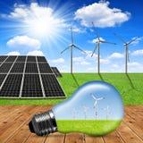 在背景太阳电池板和风轮机的Eco电灯泡 库存照片
