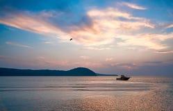 在背景日落的快速汽艇 免版税库存照片