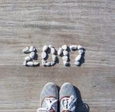 在背景木码头上的2017块被计划的石头 图库摄影