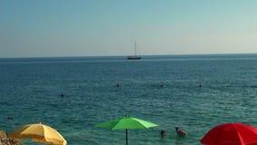 在背景游泳者和游艇的红色黄绿色阳伞 股票视频