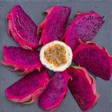 在背景特写镜头的果子被切的异乎寻常的桃红色龙和passionfruit 甜热带水果、水多的pitaya和西番莲果裁减 库存图片