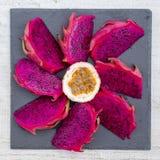 在背景特写镜头的果子被切的异乎寻常的桃红色龙和passionfruit 甜热带水果、水多的pitaya和西番莲果裁减 免版税图库摄影