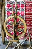 在背景的古老木手纺车刺绣针的种族样式在红色和黑色 免版税图库摄影