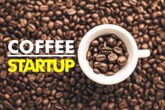 在背景的咖啡杯与消息`咖啡起始的` 免版税图库摄影