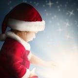 在背景的圣诞节儿童开放礼物与闪闪发光和闪烁 免版税库存照片
