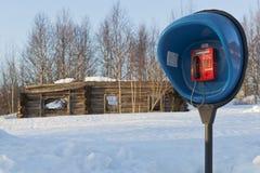 在背景的投币式公用电话破坏了偏僻地区俄国人的木房子 库存图片