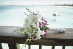 在背景的新娘花束和海滩视图 免版税库存图片
