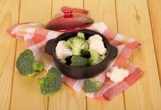 在背景的砂锅用未加工的硬花甘蓝和花椰菜点燃木头 库存照片