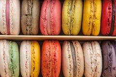 在背景的箱子堆积的堆五颜六色的蛋白杏仁饼干 免版税库存图片