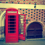 在背景的红色电话箱子砖墙 库存照片
