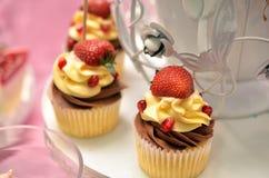 在背景的草莓杯形蛋糕 库存图片