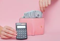 在背景的计算器用妇女取消金钱的` s手从在桃红色背景的钱包与拷贝空间 库存照片