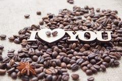 在背景的词`我爱你`溢出了咖啡 库存照片