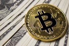在背景的Cryptocurrency Bitcoin硬币与美元 免版税图库摄影