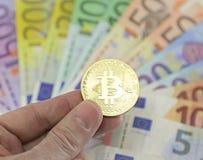 在背景的Goden BITCOIN和被弄脏的欧洲钞票 库存照片