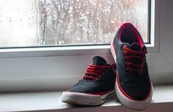 在背景窗口的黑和红色运动鞋在下雨天关闭 免版税库存图片