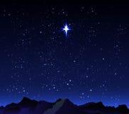 在背景繁星之夜天空的山与一个大星 免版税库存照片