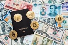 在背景,证明身分的黑护照 反对纸币,美元,中国元CNY,金属铸造, bitcoin 库存图片