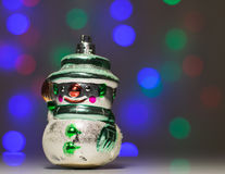 在背景bokeh的减速火箭的圣诞节玩具雪人 免版税库存图片